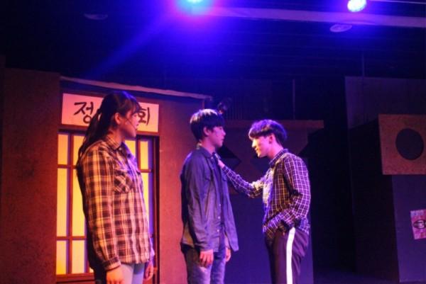 공연사진2 - 남자2명이 서로 보고있고 그걸 여자가 바라본다.