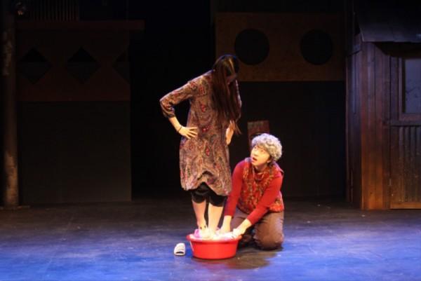 공연사진4 - 여자가 발로 밟으며 이불빨래 하는 모습.