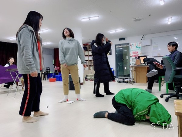 공연연습사진2 - 한명이 바닥에 엎드려있고 나머지는 주위에 서서 연습중인 모습
