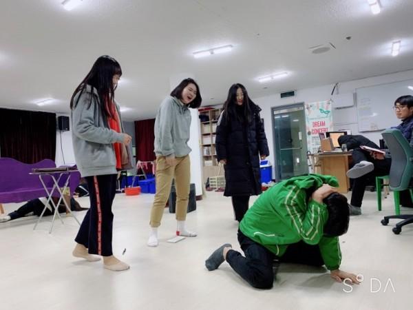 공연연습사진6 - 한명이 바닥에 엎드려 있고, 뒤에서 3명이 그걸 보며 웃는 사진