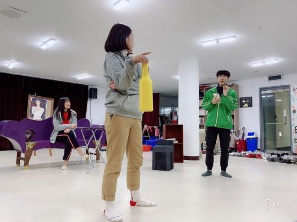 공연연습사진7 - 노란병을 들고있는 여자와 수첩을든 남자가 서로 마주보며 서있다.